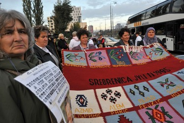 Bosnian Muslim women from Srebrenica, hold a hand woven carpet with the names of their killed relatives embroidered, before boarding a bus, in Sarajevo, early on 24 October, 2009. Buses carrying about 200 Bosnian Muslim family members of the war victims departed Sarajevo to the Hague, Netherlands,  to demand swift trial and severe punishment for Serb leader Radovan Karadzic, facing war crimes trial, scheduled to begin, early on 26 October. Families of victims from Srebrenica along with others from Bosnia are planning to hold rallies in front of the Hague tribunal building until they are assured that Karadzic trial is fair to the victims. AFP PHOTO ELVIS BARUKCIC (Photo credit should read ELVIS BARUKCIC/AFP/Getty Images)